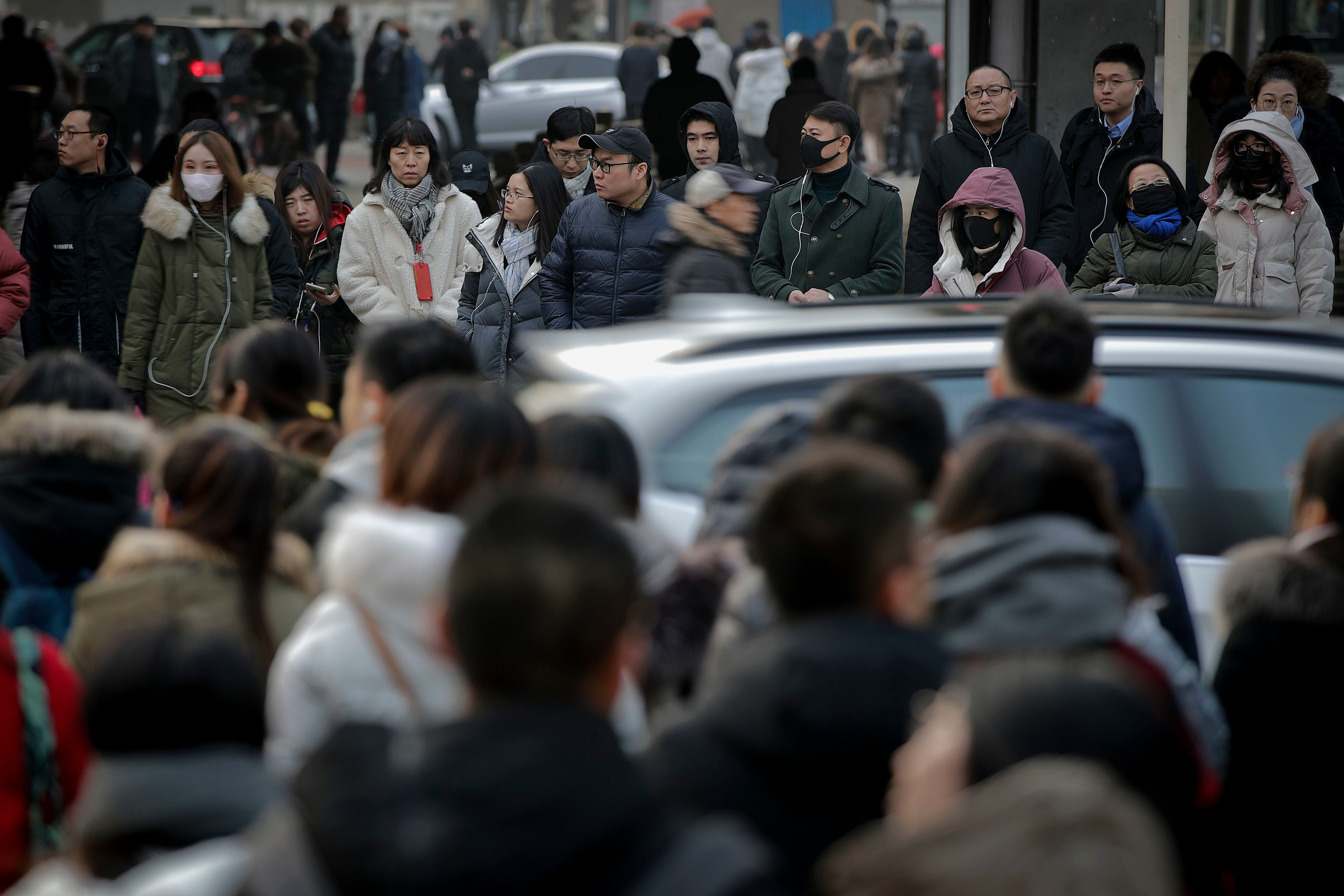 Pedestrians wait to cross a traffic intersection at the Central Business District in Beijing, . China's 2018 trade surplus with the United States surged to a record $323.3 billion but exports contracted in December as the delayed impact of President Donald Trump's tariff hikes started to depress demand. Global exports shrank 4.5 percent in December, reflecting weak consumer demandTrade, Beijing, China - 14 Jan 2019