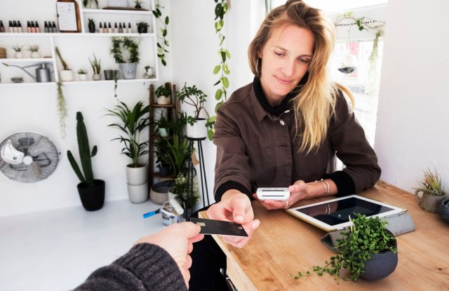 MODEL RELEASED Female owner of plant shop receiving credit card from customer for payment of small String of Pearls plant in black pot.VARIOUS