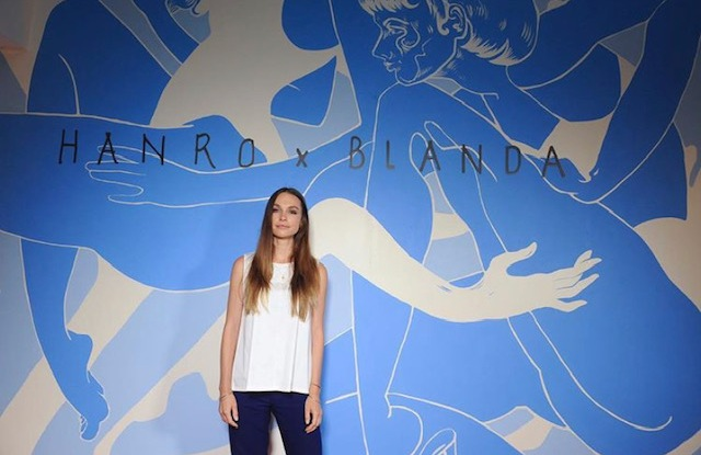 Contemporary artist Blanda in front of the mural she painted at Hanro's Beverly Hills' location.