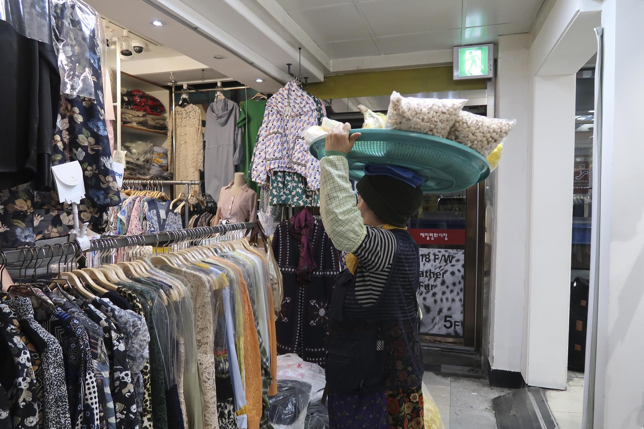 A woman sells snacks to stall operators at Dongdaemun.