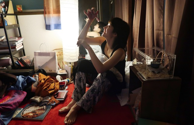Kom I and her pet snake in her Tokyo flat.