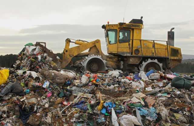 Compactor moving rubbish on landfill tip, Dorset, England, FebruaryNature