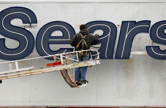 In this Feb. 13, 2012 photo, a worker repairs the Sears sign outside the Sears Grand store in Solon, Ohio. Sears Holdings said, it will separate its smaller hometown stores, outlets and some hardware stores in a deal expected to raise $400 million to $500 million as it seeks to regain profitability and market shareEarns Sears, Solon, USA