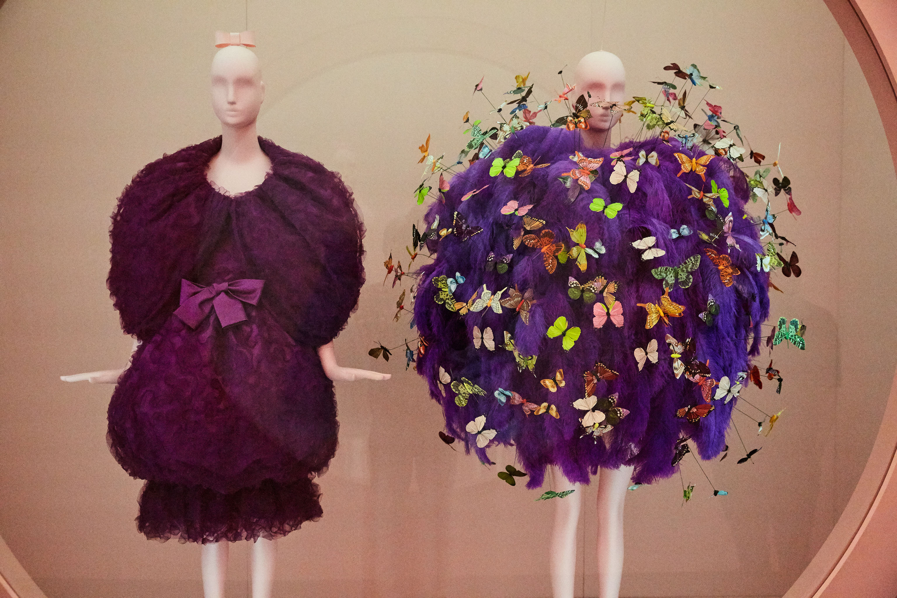 A Cristóbal Balenciaga evening ensemble from fall 1961 and a fall 2018 one from Jeremy Scott for Moschino embroidered with purple ostrich feathers, and polychrome printed feather and paper butterflies.