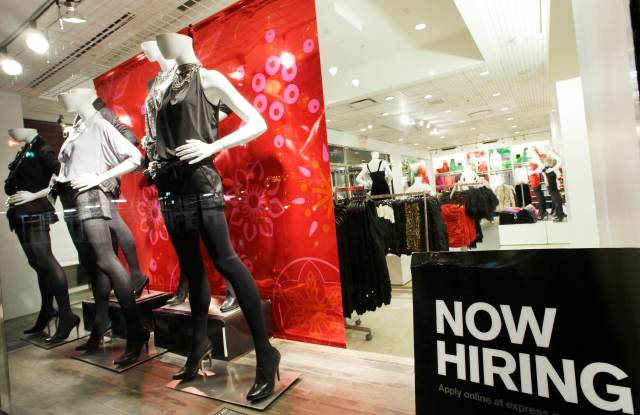 "A ""now hiring"" sign is shown in the window of an Express clothing store, in New York. Slightly more people applied for unemployment benefits last week, but first-time claims remain near their lowest level in two yearsEconomy Unemployment, New York, USA"