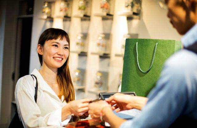 MODEL RELEASED Smiling Japanese woman standing at counter in clothing store, paying with credit card.VARIOUS