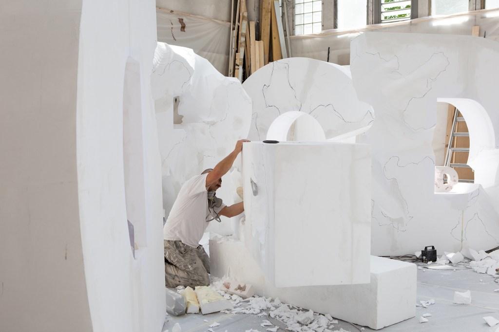 A man working on Daniel Arsham's Dior show set.