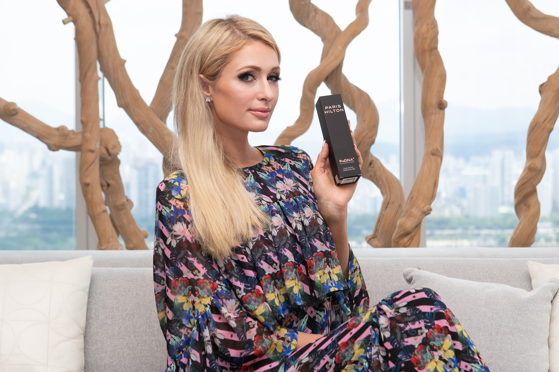 Paris Hilton holds up her ProD.N.A. skincare line.