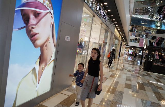 Chinese consumers walk at a shopping mall in Beijing, China, 28 May 2019. According to media reports, middle-class citizens are expressing their concerns over how the China-US trade war will affect their lives as food prices and business costs continue to rise.China-US trade war affects middle class in China, Beijing - 28 May 2019