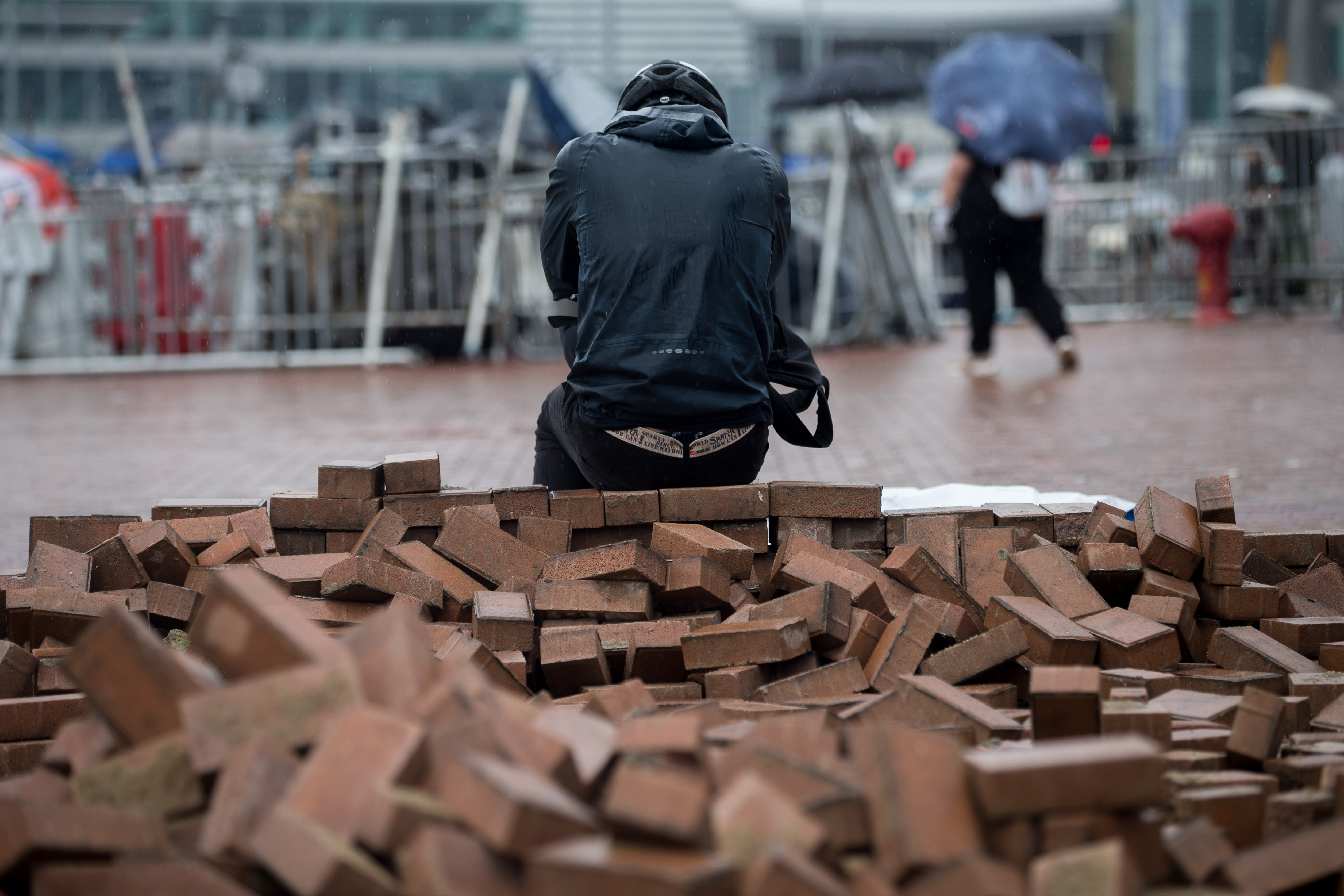 A man rests on a pile of bricks gathered by protesters.
