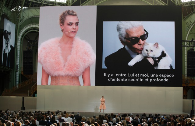 """Model Cara Delevingne is seen on a giant screen as she speaks to the invited guests during the event named """"Karl for Ever"""" at the Grand Palais in Paris, France, . The event pays tribute to late German fashion designer Karl Lagerfeld who died Feb. 19, 2019Lagerfeld Tribute, Paris, France - 20 Jun 2019"""