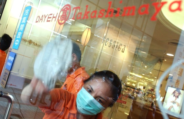 An employee wipes the glass doors of the Takashimaya department store