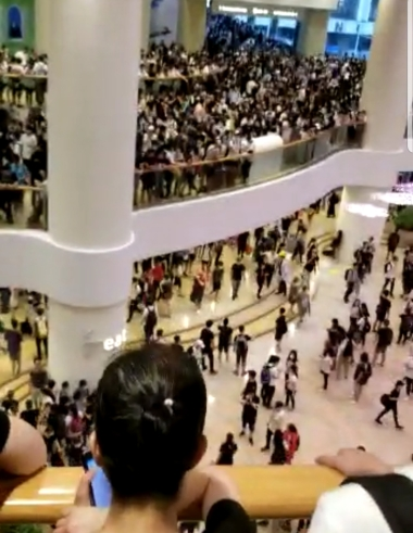 A screenshot from a video showing crowds of protesters streaming into Pacific Place mall.