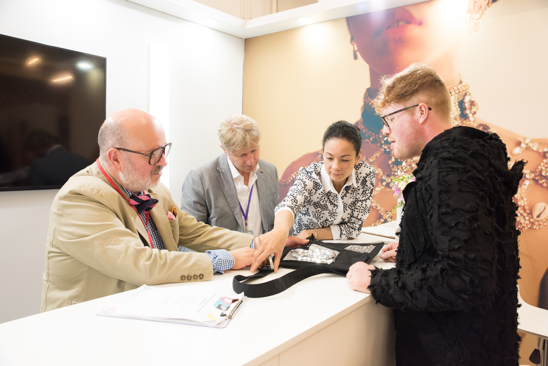 One design student talking to company representatives from Swarovski at Graduate Fashion Week
