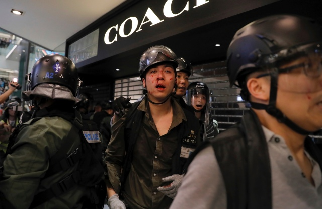 An injured policeman is escorted out by colleagues from New Town Plaza mall.
