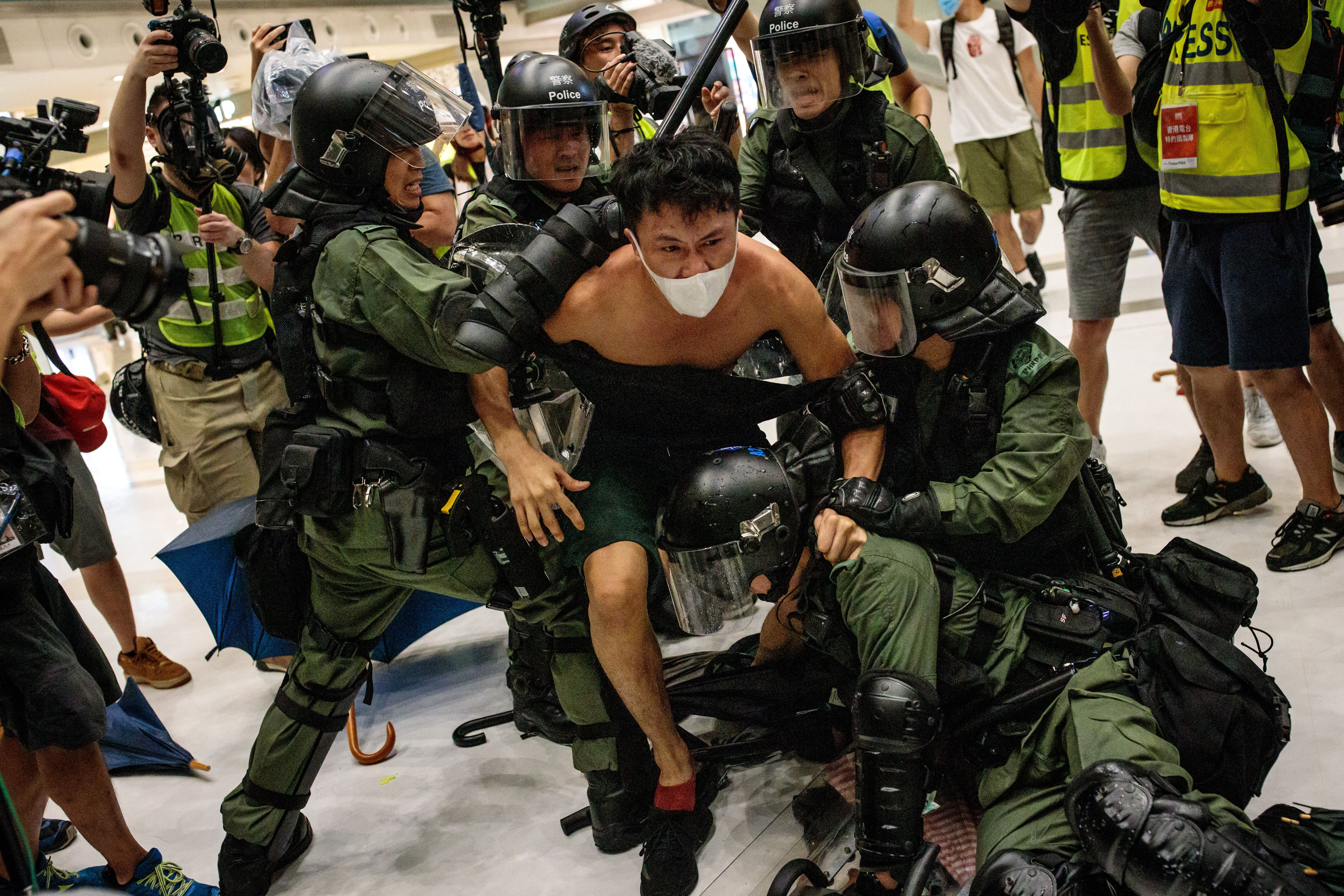 A protester tries to break free of riot police. Police later said 37 people were arrested from Sunday's rally.