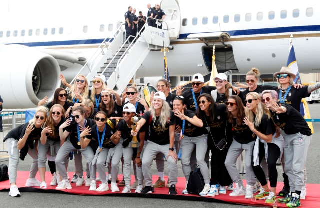Julie Ertz, Megan Rapinoe, Alex Morgan. Members of the United States women's soccer team, winners of a fourth Women's World Cup, celebrate and pose with the trophy by their plane after arriving at Newark Liberty International Airport, in Newark, N.J. Julie Ertz holds the trophy, Megan Rapinoe, front right, gestures, and Alex Morgan, back left, also gesturesWWCup US Returns Home, Newark, USA - 08 Jul 2019