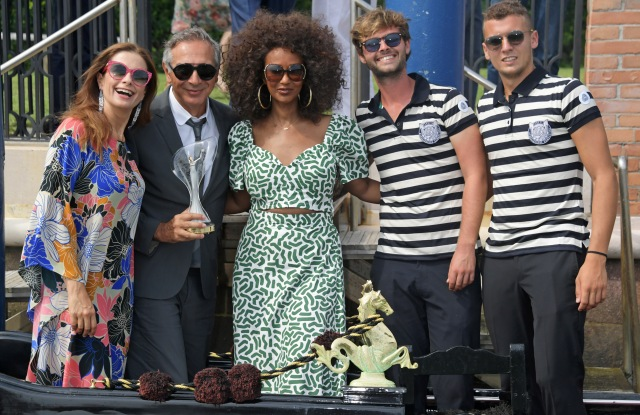 VENICE, ITALY - AUGUST 28: (L to R) Livia Firth, Carlo Capasa and Iman pose with Gondoliers at The Green Carpet Fashion Awards lunch, hosted by CNMI and Eco-Age, at Belmond Cipriani Hotel on August 28, 2019 in Venice, Italy. Pic Credit: Dave Benett