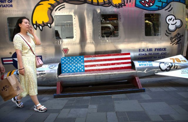 A woman walks past a bench shaped like a missile painted with the U.S. flag outside of a clothing store at a shopping mall in Beijing, . President Donald Trump and Chinese President Xi Jinping agreed to a new cease-fire Saturday in a yearlong trade war during their meeting on the sidelines of a conference in Japan, averting, at least for now, an escalation feared by financial markets and the business community while negotiations continueTrump, Beijing, China - 29 Jun 2019