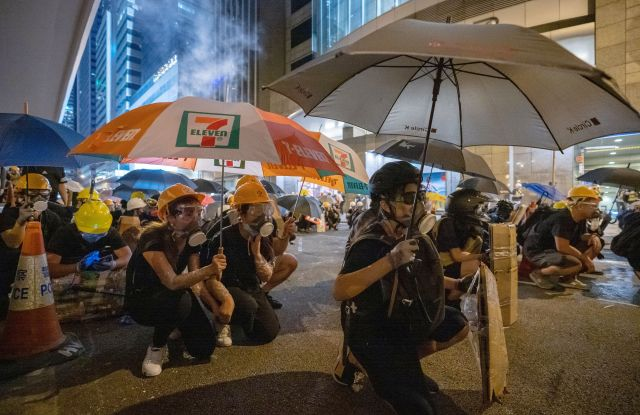 Demonstrators use umbrellas and home made shields to protect themselves from police rubber bullets firing against them during the anti-government protest. Protests in Hong Kong, China