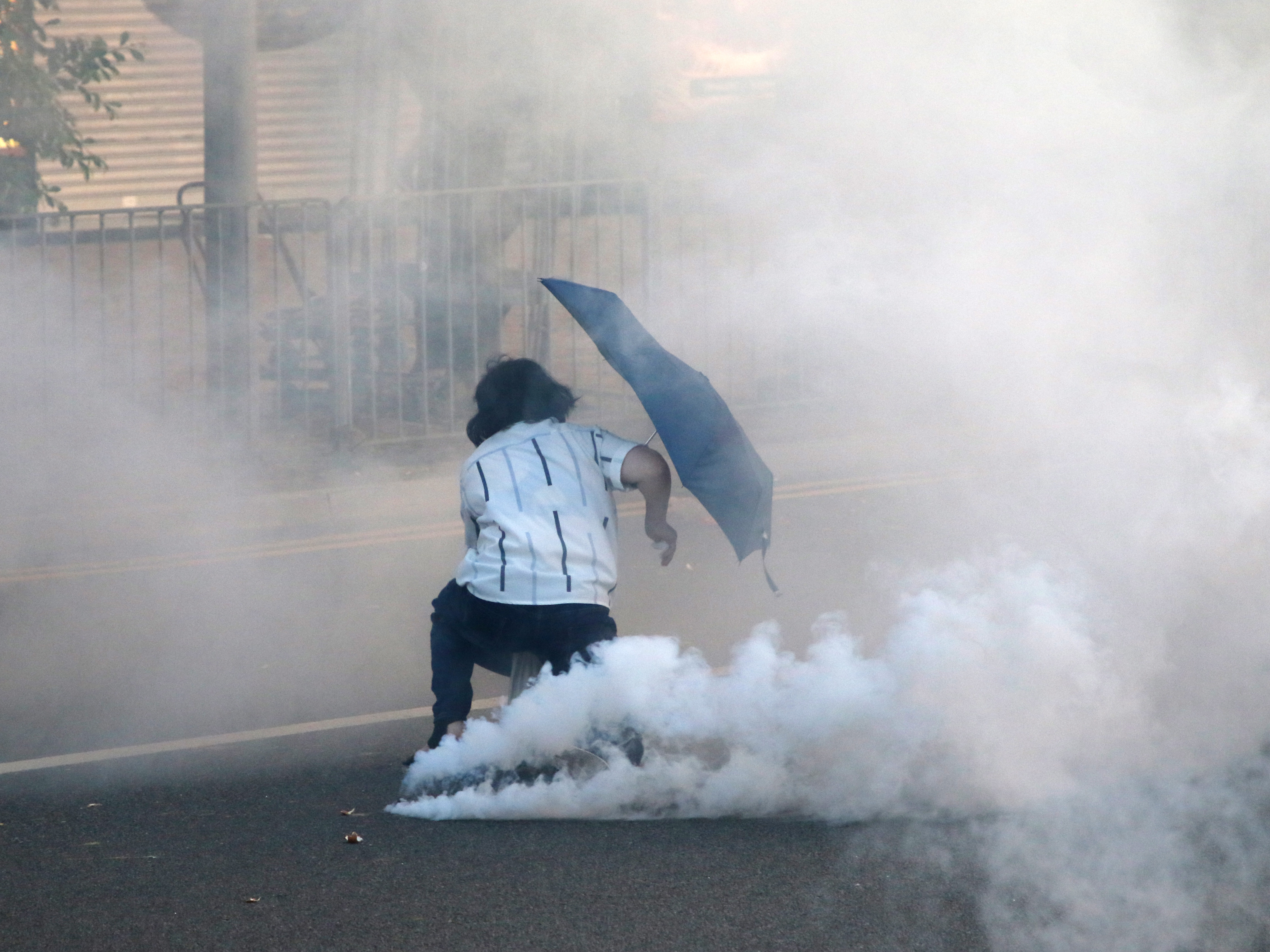 A woman try to negiotate with police collapse in the tear gas during the confrontation in Hong Kong Protests/