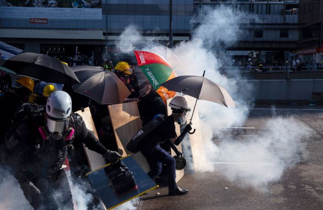 Anti-extradition protesters react after police fired tear gas at them in the Admiralty area of Hong Kong, China