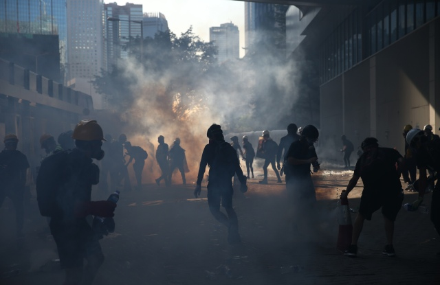 Anti-extradition protesters react after police fired tear gas at them in the Admiralty area of Hong Kong, China, 05 August 2019. Hong Kong is in the midst of a day of citywide strike following a ninth consecutive weekend of multiple anti-extradition rallies and intense clashes between demonstrators and police over the now suspended extradition bill to China.Anti-extradition protesters clash in Hong Kong, China - 05 Aug 2019