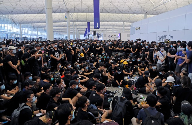 Protesters gather near an information board during a protest at the Hong Kong International Airport, . One of the world's busiest airports canceled all flights after thousands of Hong Kong pro-democracy protesters crowded into the main terminal Monday afternoonProtest, Hong Kong, Hong Kong - 12 Aug 2019