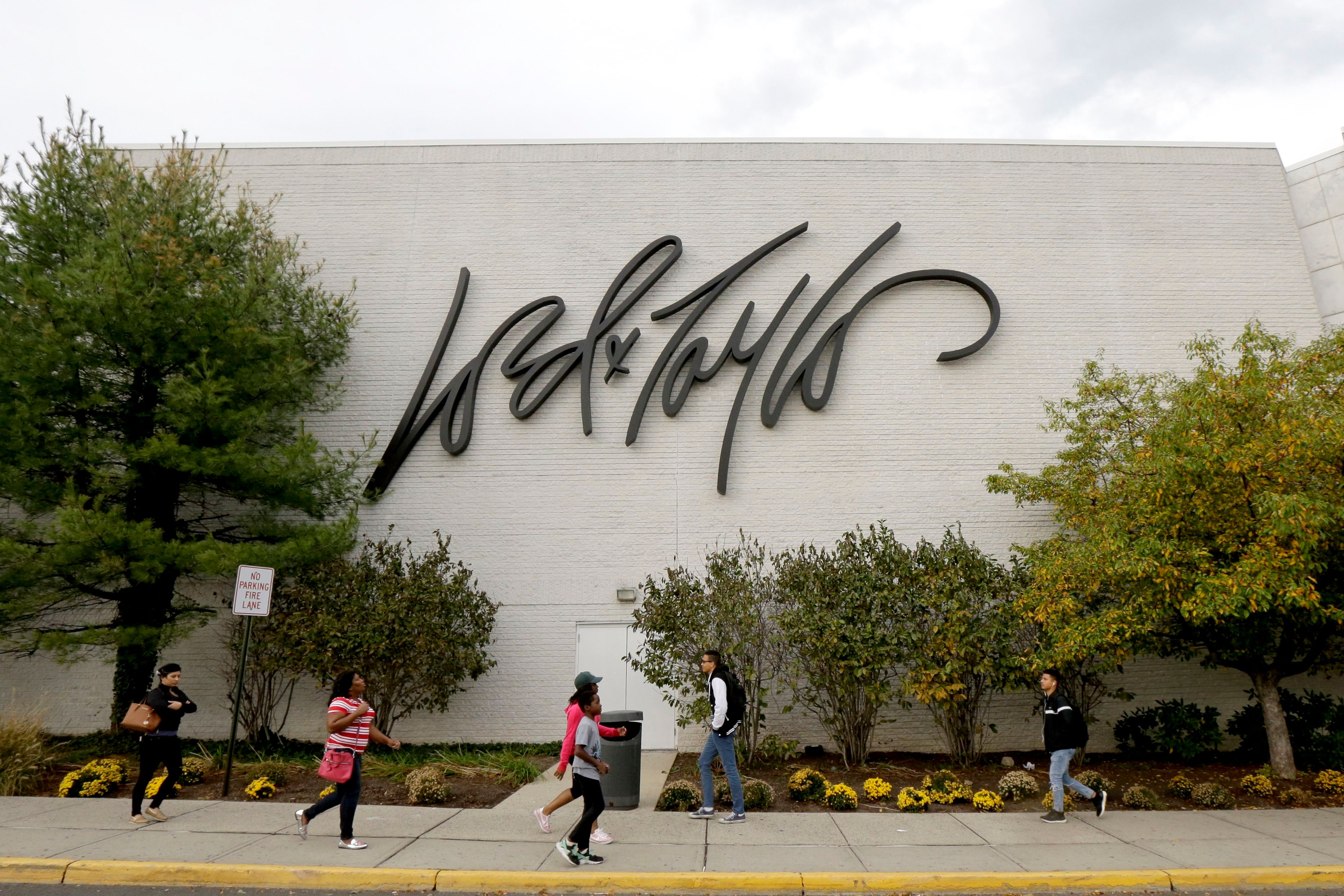 People walk on a sidewalk along the entrance to Lord & Taylor department store at Garden State Plaza, in Paramus, N.JNew Jersey Retailer Stores, Paramus, USA - 25 Oct 2017