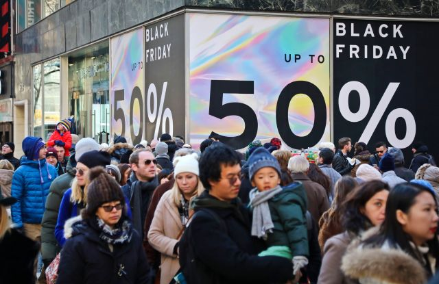 Crowds walk past a large store sign displaying a Black Friday discount in midtown Manhattan, in New York. The holiday shopping season presents a big test for a U.S. economy, with overall growth so far this year relying on a burst of consumer spendingHoliday Black Friday, New York, USA - 23 Nov 2018