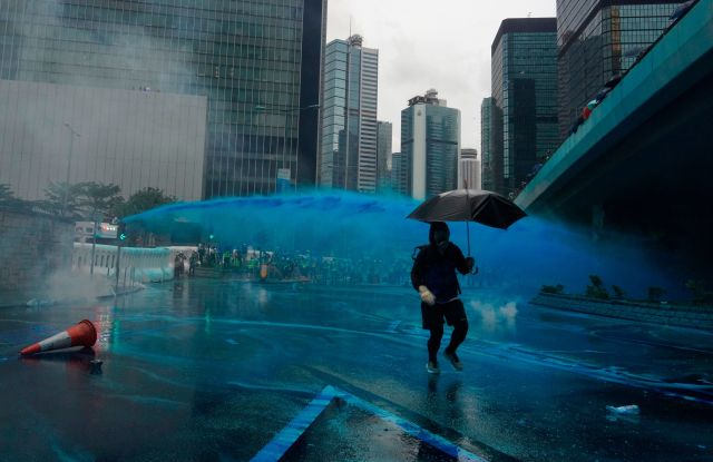 A protestor runs for cover as police fire blue-colored water from water cannons in Hong Kong.