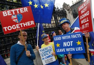 Steve Bray, an anti Brexit campaigner, right stands with fellow campaigners as they hold their placards and flags outside the Houses of Parliament in London, . The British government insisted Thursday that its forecast of food and medicine shortages, gridlock at ports and riots in the streets after a no-deal Brexit is an avoidable worst-caseBrexit, London, United Kingdom - 12 Sep 2019