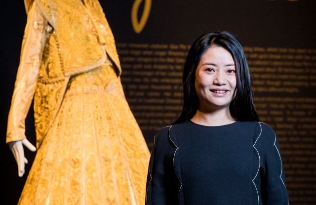 Guo Pei, stands alongside her gold traditional bridal dress at Sotheby's
