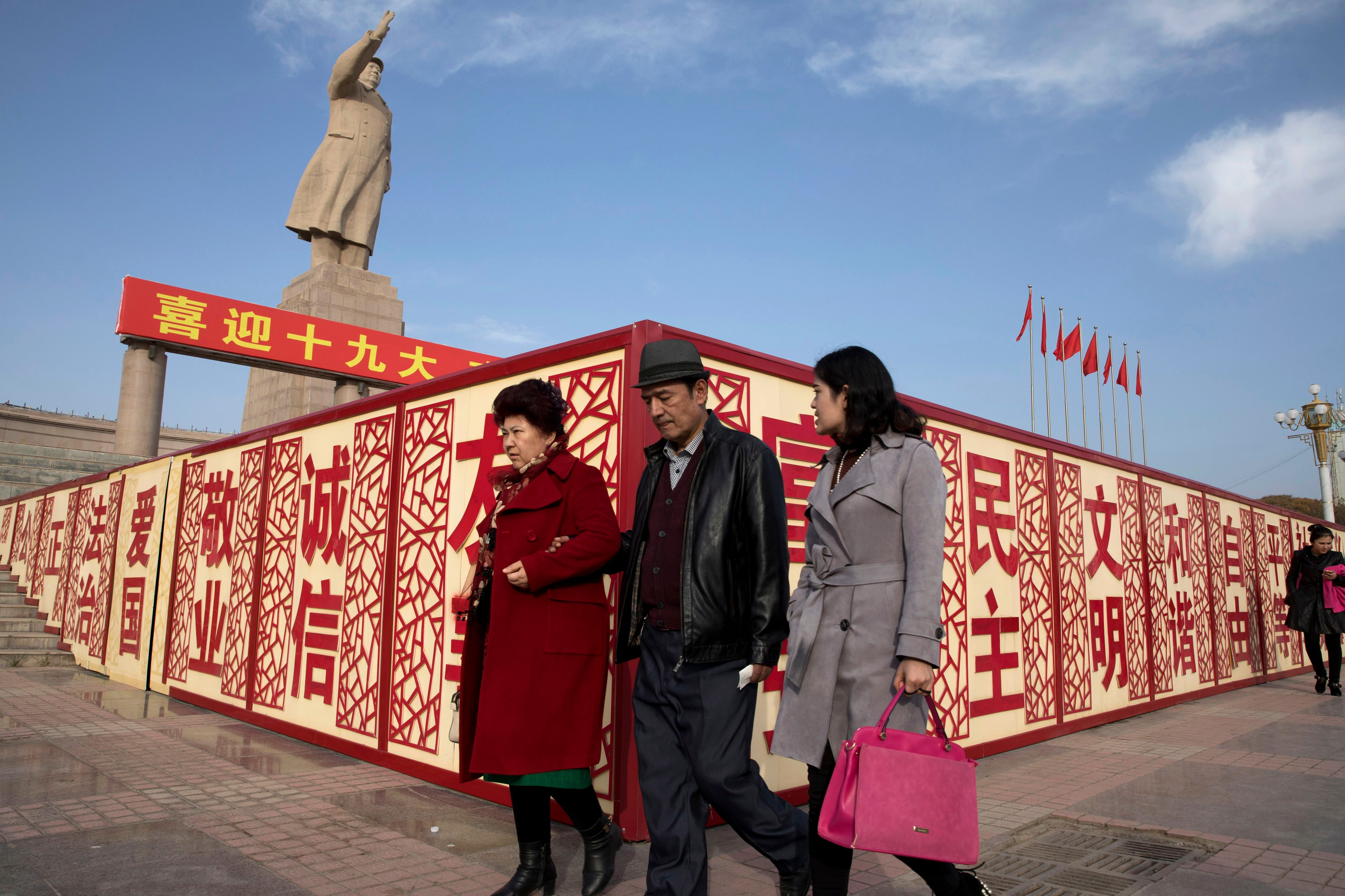 """Residents walk past a statue showing Mao Zedong near billboards with the words for """"Welcome 19th Congress,"""" """"Patriotism"""" and """"Democracy"""" near a square in Kashgar in western China's Xinjiang region. Authorities are using detentions in political indoctrination centers and data-driven surveillance to impose a digital police state in the region of Xinjiang and its Uighurs, a 10-million strong, Turkic-speaking Muslim minority Beijing fears could be influenced by extremismDigital Police State, Kashgar, China - 04 Nov 2017"""