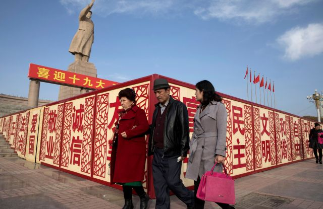 "Residents walk past a statue showing Mao Zedong near billboards with the words for ""Welcome 19th Congress,"" ""Patriotism"" and ""Democracy"" near a square in Kashgar in western China's Xinjiang region. Authorities are using detentions in political indoctrination centers and data-driven surveillance to impose a digital police state in the region of Xinjiang and its Uighurs, a 10-million strong, Turkic-speaking Muslim minority Beijing fears could be influenced by extremismDigital Police State, Kashgar, China - 04 Nov 2017"