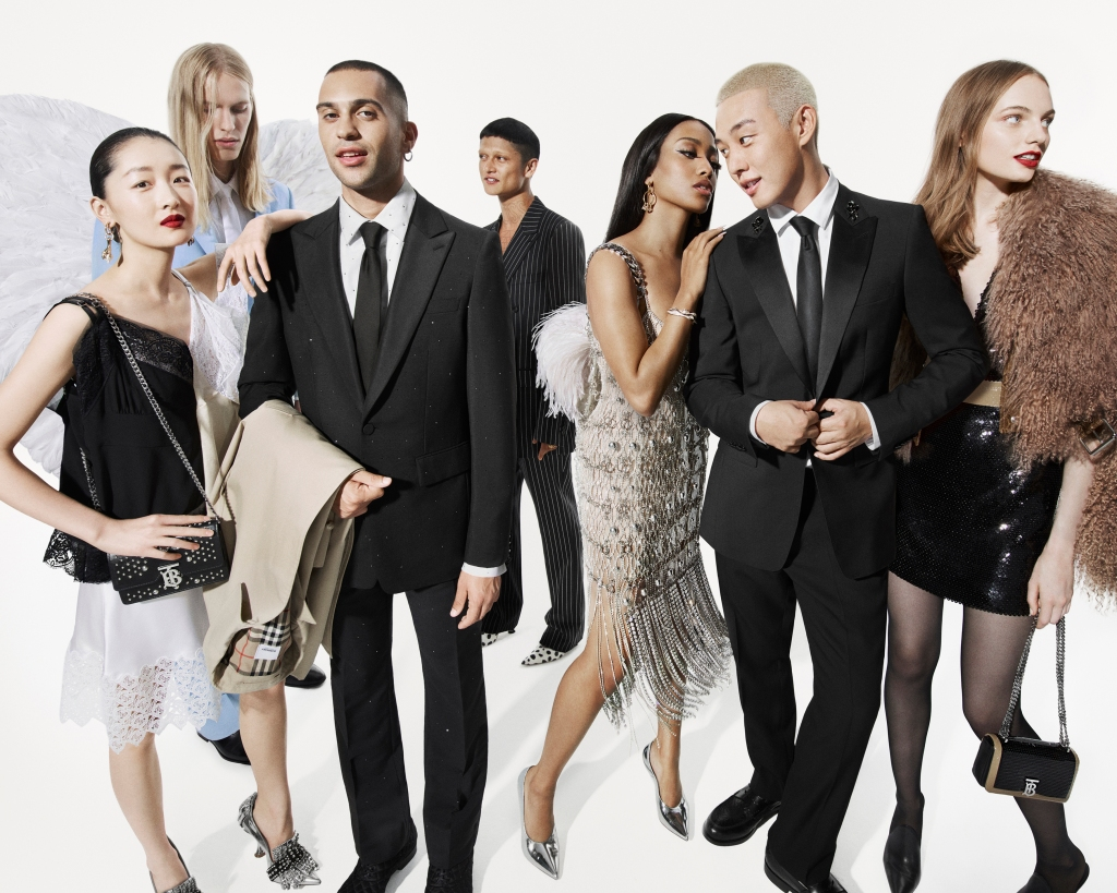 Mahmood on the left wearing a dark suit and holding a Burberry trench coat for the brand's 2019 holiday campaign shot by Mert Alas & Marcus Piggott.