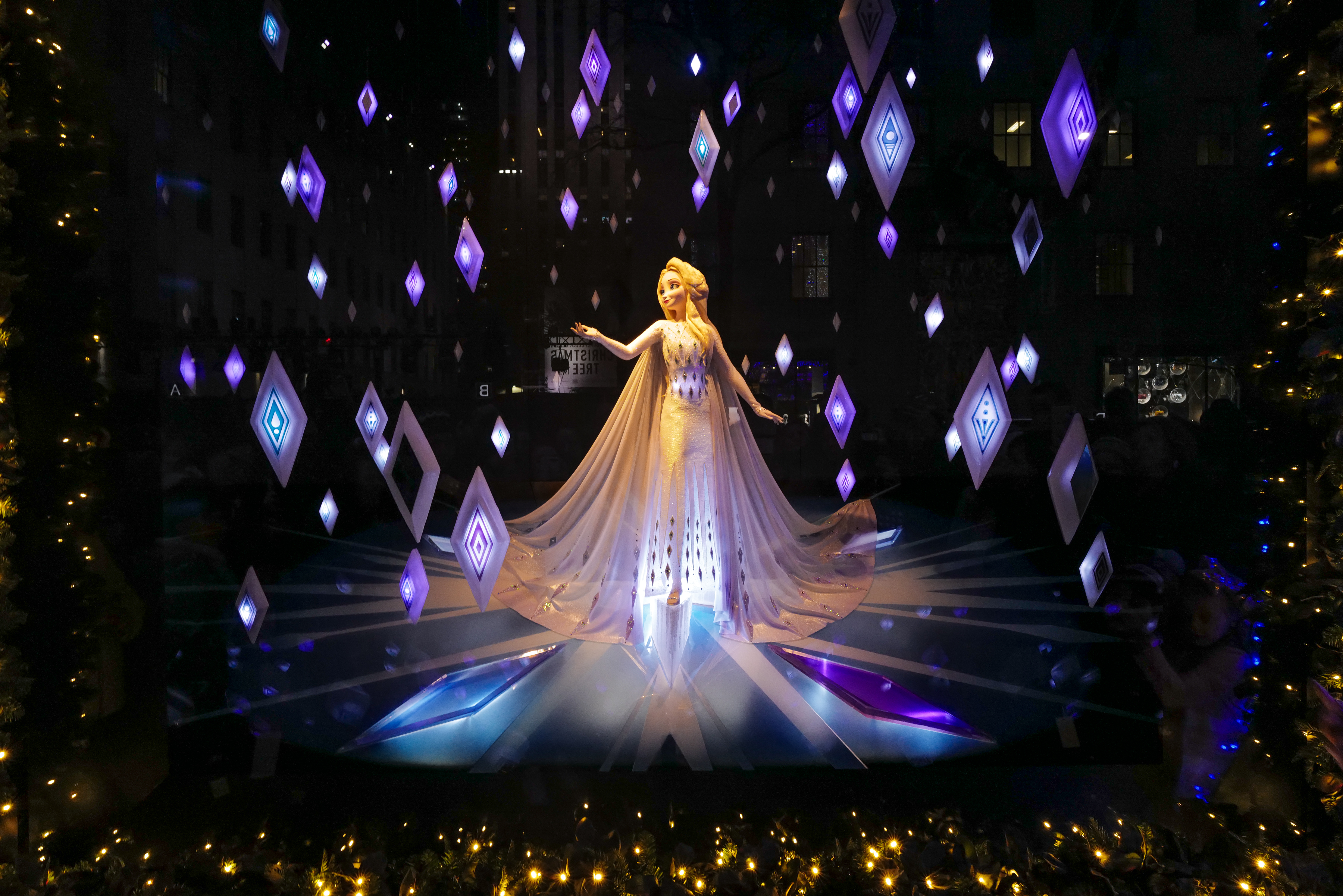 """Princess Elsa smiles from Saks Fifth Avenue's """"Frozen 2""""-themed holiday windows."""
