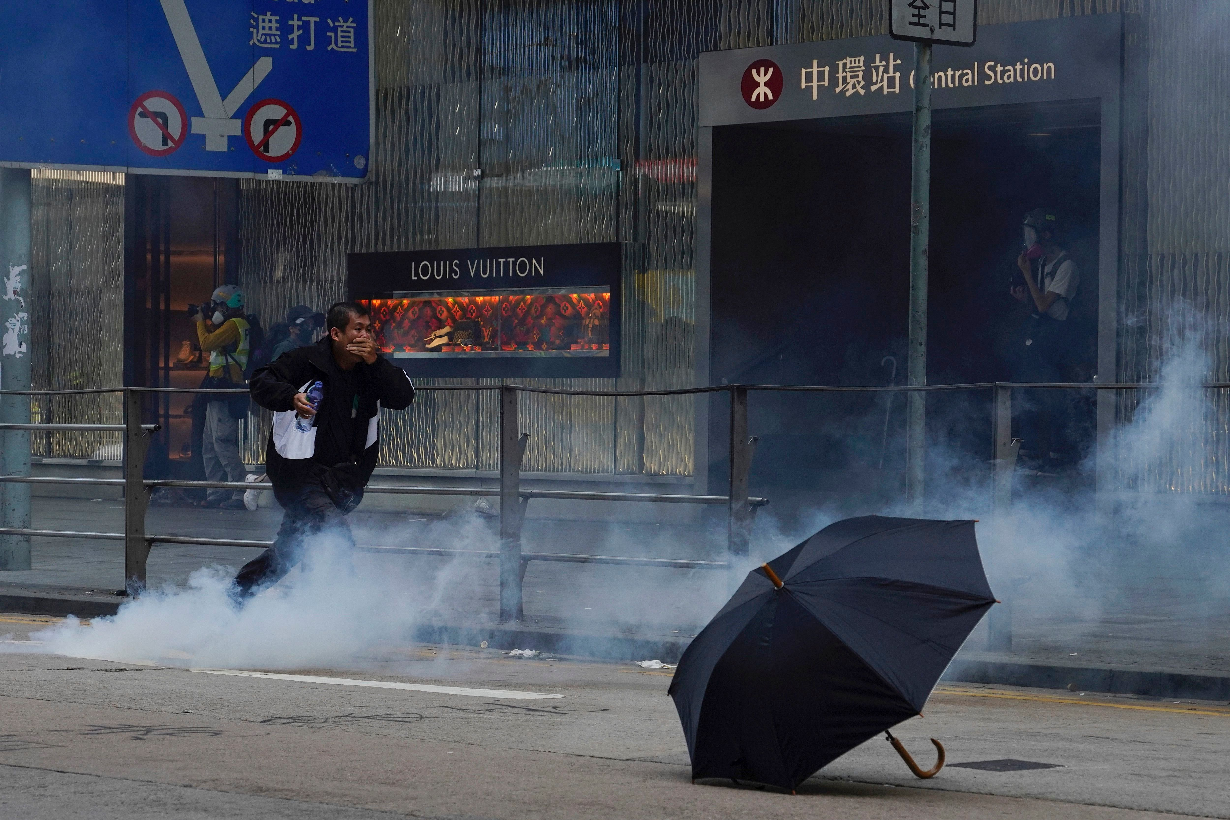 A man runs away from tear gas fired by riot police in Central in Hong Kong, in front of a Louis Vuitton store.