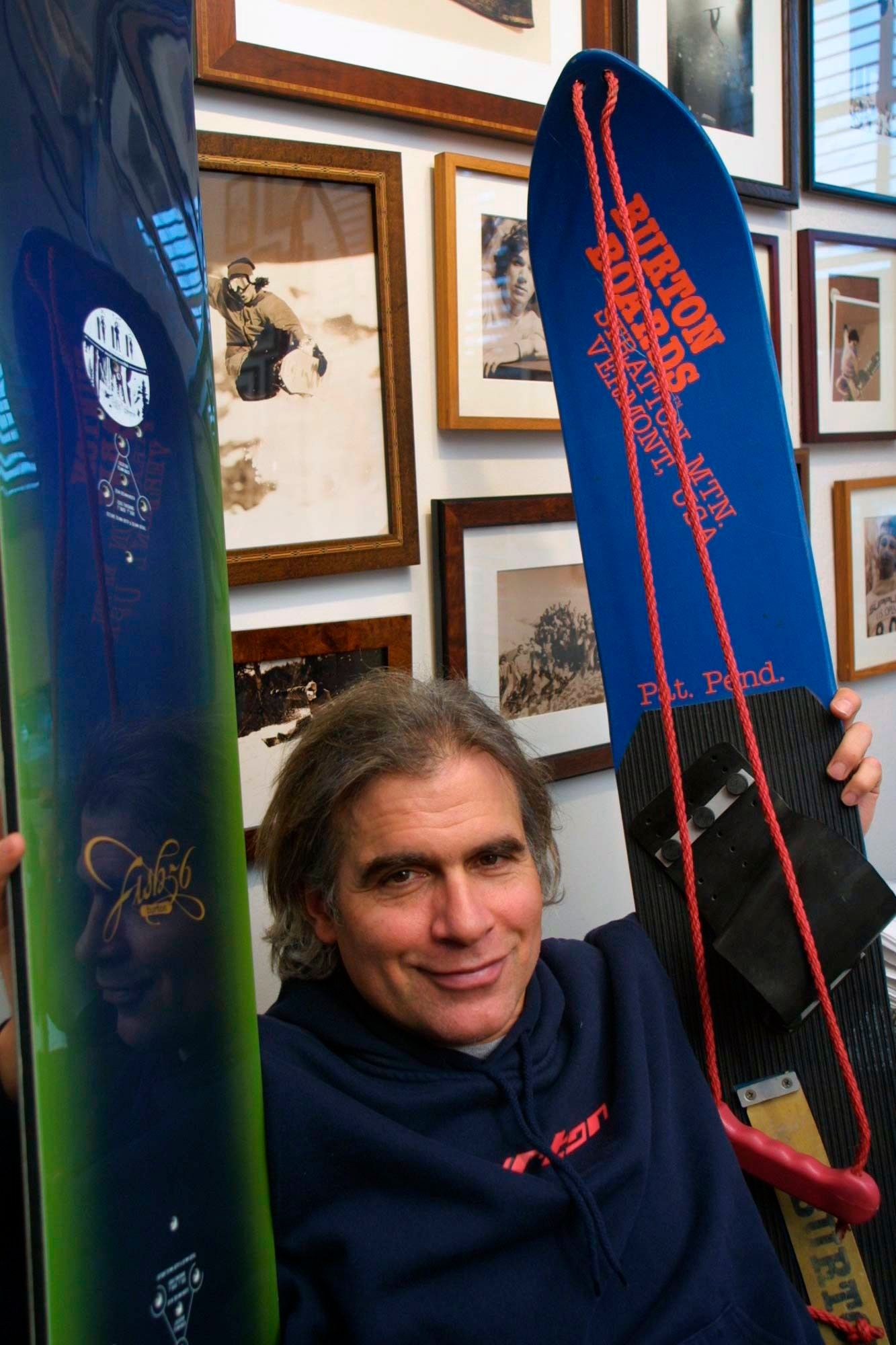 JAKE BURTON CARPENTER. Jake Burton Carpenter, owner of Burton Snowboards, shows an early model, right, and one of the newer snowboards, left, in his office in Burlington, Vt. Carpenter, the innovator who brought the snowboard to the masses and helped turn the sport into a billion-dollar business, has died after a recurring bout with cancer. He was 65. Officials from the company he founded, Burton Snowboards, told The Associated Press of his deathObit Jake Burton, BURLINGTON, USA - 08 Mar 2002