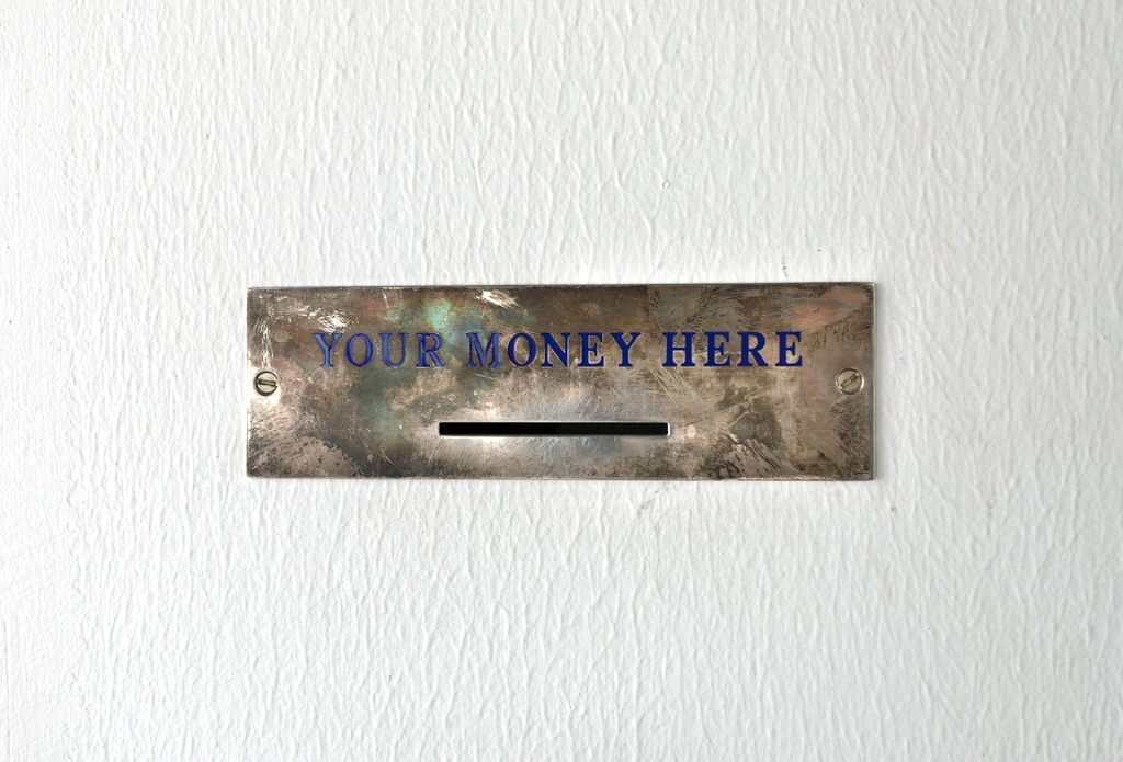 Lara Favaretto Your Money Here 2008 solid silver label, blue Savoia enamel, screws cm 7 x 16 Collection Philip Aarons and Shelley Fox Aarons, New York Installation view, 'Lara Favaretto - Just Knocked Out', MoMA PS1 New York
