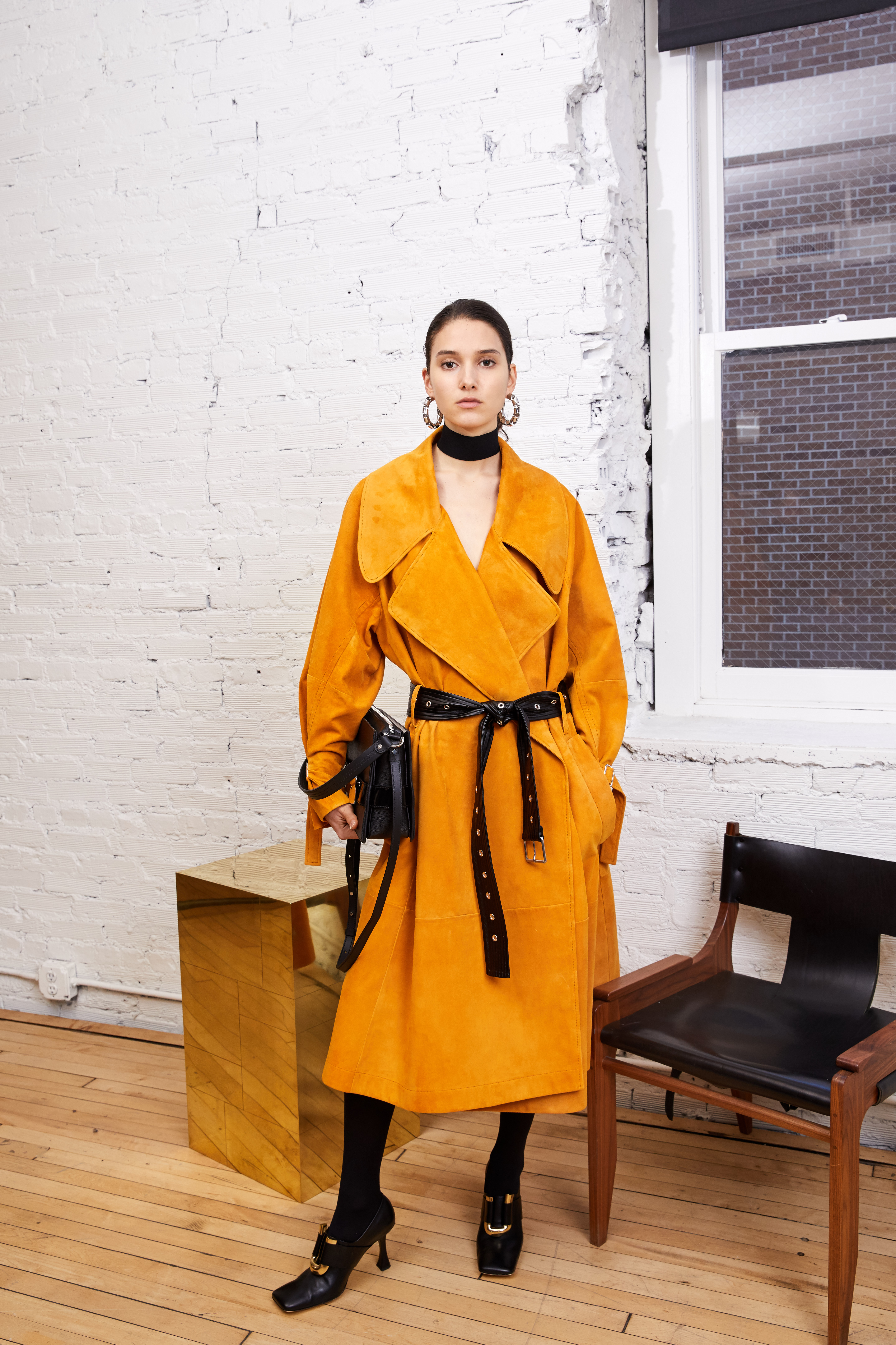 From pre-fall, a grommeted belt adds edge to a roomy suede coat, shown with a leather Trapeze buckle bag and square-toed pumps. Accessories development is a major focus of the brand.