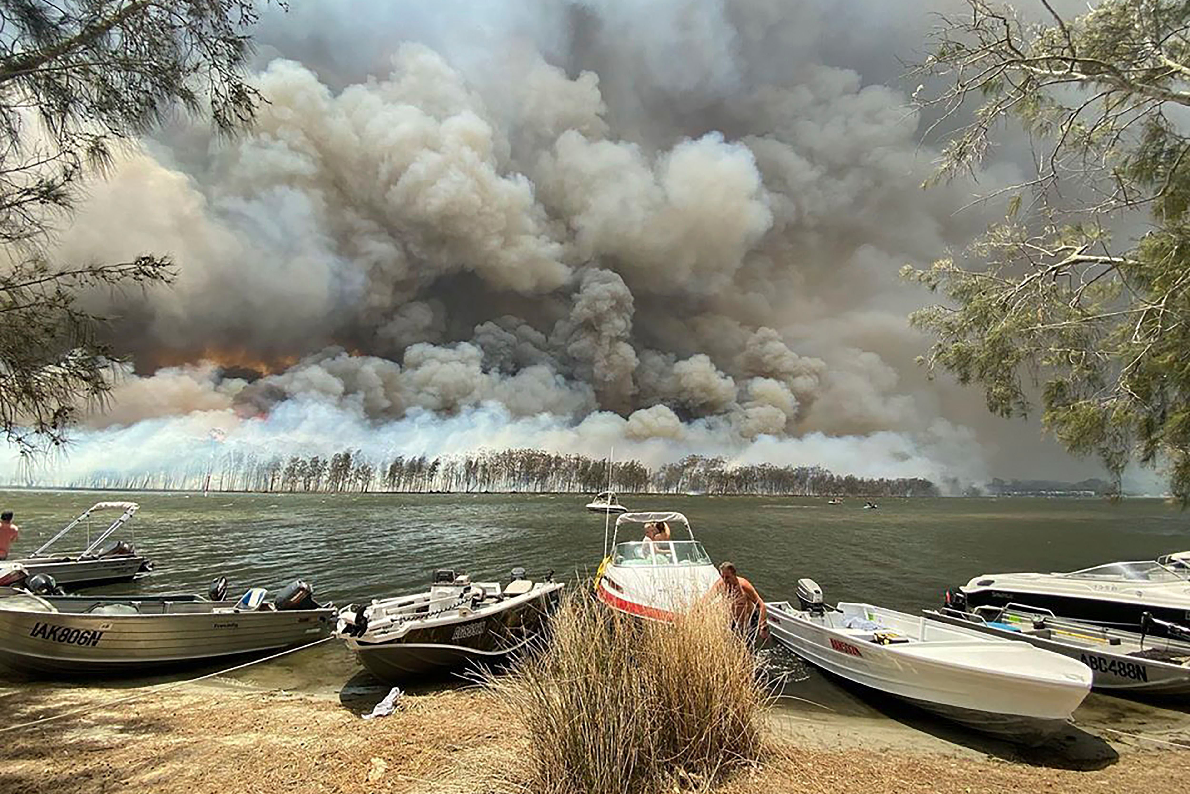 Boats are pulled ashore as smoke and wildfires rage behind Lake Conjola, Australia, . Thousands of tourists fled Australia's wildfire-ravaged eastern coast Thursday ahead of worsening conditions as the military started to evacuate people trapped on the shore further southWildfires, Conjola, Australia - 02 Jan 2020