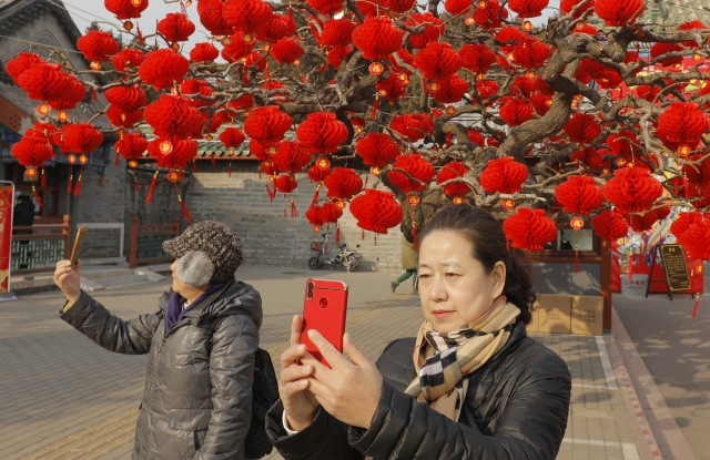 People take photos near a tree decorated with red lanterns ahead of the upcoming Chinese Lunar New Year at Ditan Park in Beijing, China.