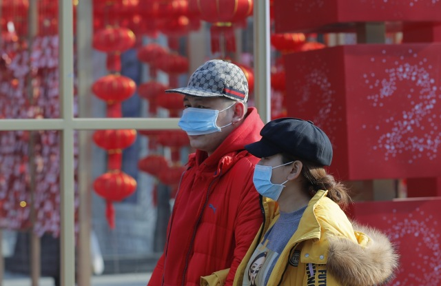 Chinese people wear masks in a street of Beijing, China.