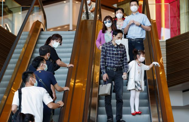 People wear protective masks while riding an escalator at a shopping mall.