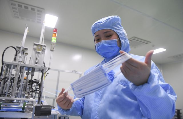 A staff member works at the producing workshop of face mask in a medical devices company in Nan'an District of southwest China's Chongqing