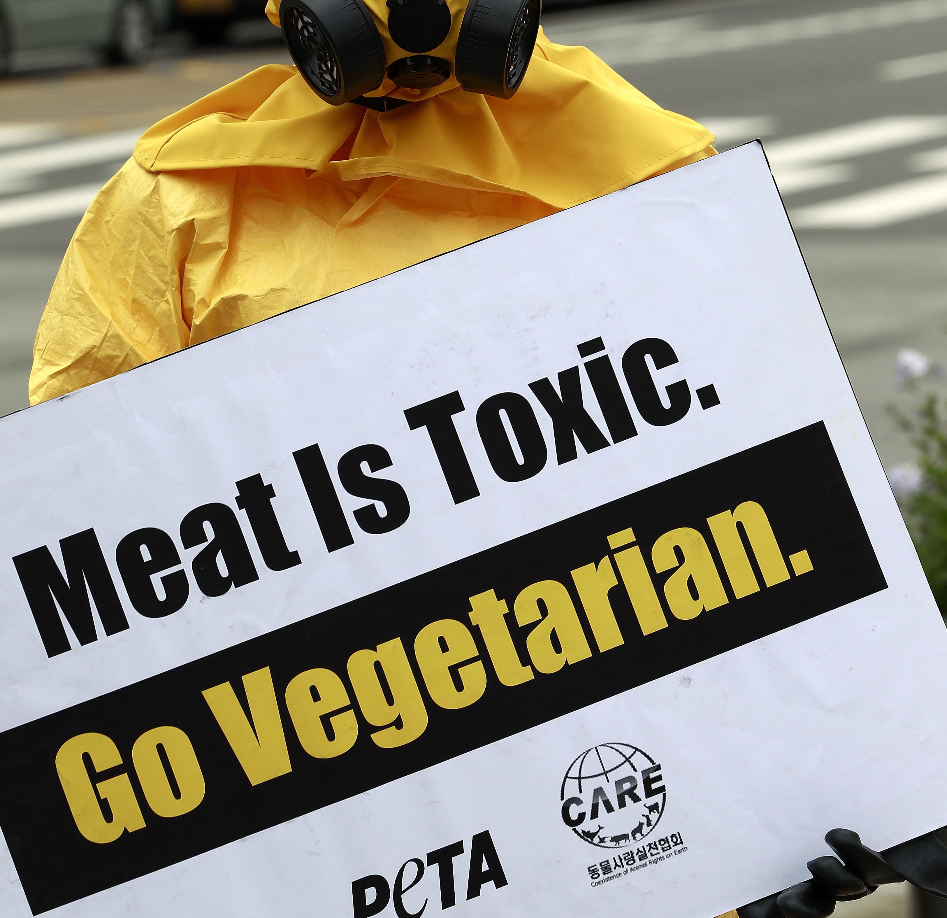 A Member of 'People For the Ethical Treatment of Animals' (peta) Protests Wearing a Yellow Hazardous Material Suit with a Gas Mask and Holds a Signs That Reads 'Meat is Toxic Go Vegetarian' on the Street in Seoul South Korea 24 August 2012 Korea, Republic of SeoulSouth Korea Peta Protest - Aug 2012