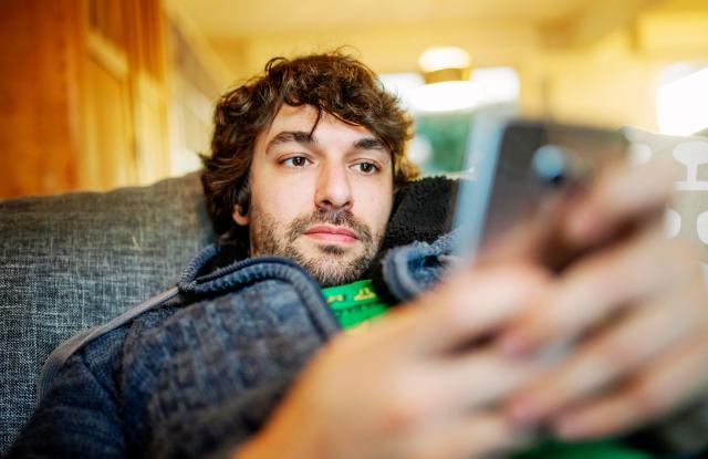 MODEL RELEASED Young man lies relaxed with smartphone on sofa, GermanyVARIOUS