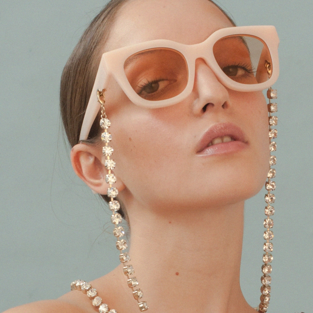 A pair of sunglasses embellished with a pearl chain accessory from Huma Sunglasses.