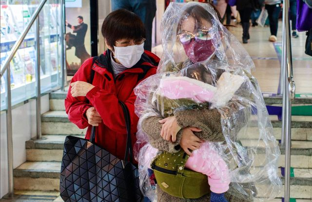 A woman with her child wrapped in a plastic sheet in Hong Kong.